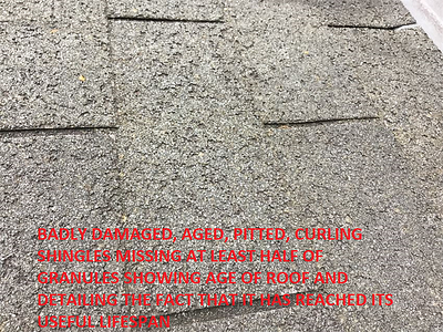 Badly damaged, aged, pitted, curling shingles missing at least half of granules showing the age of the roof and detailing the fact that it has exceeded its useful lifespan.