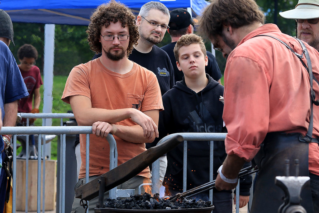 . The 15th annual Blacksmith Art and Renaissance Festival was held on Saturday, September 29, 2018. Watching blacksmiths work, from left, is Jason Hilley from Connecticut, James Danzl from Fitchburg and Mark Callerg, 14, from Ashburnham. SENTINEL & ENTERPRISE/JOHN LOVE