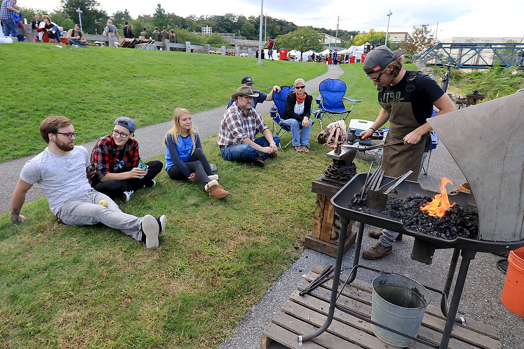 . The 15th annual Blacksmith Art and Renaissance Festival was held on Saturday, September 29, 2018. Some festival goers watch blacksmith David Caruso of Ashburnham as he works during the festival. SENTINEL & ENTERPRISE/JOHN LOVE