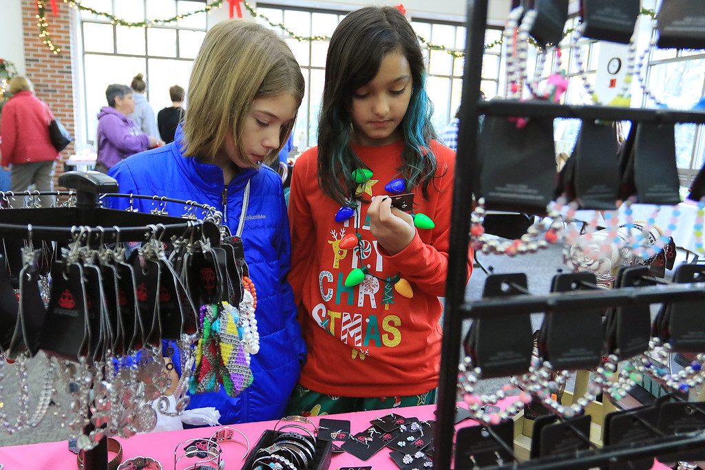 . Holiday Fair and Cookie Sale was held at the Hazen Memorial Library in Shirley on Saturday, November 3, 2018. Carolyn Mason and Kaili Dawson of Shirley look at some jewelry at Melinda Palmers display at the fair. Palmer owns Love Our Habit Paparazzi Jewerly of Acton. SENTINEL & ENTERPRISE/JOHN LOVE