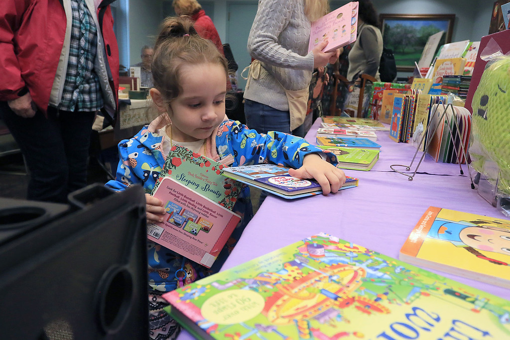 . Holiday Fair and Cookie Sale was held at the Hazen Memorial Library in Shirley on Saturday, November 3, 2018. Davina Cummings, 3, of Shirley looks for a good book to read at Usborne Books display at the fair. SENTINEL & ENTERPRISE/JOHN LOVE