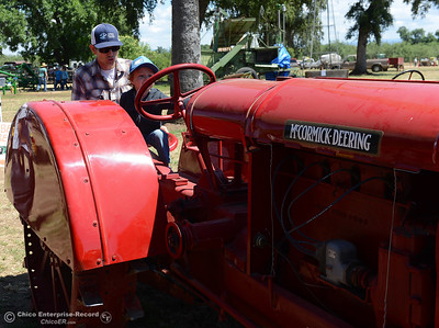 Jesse Barnett, left, and 2-year-old Waylan Barnett check out a McKormick-Deering tractor at the 15th Annual Old Fashioned Country Faire and Threshing Bee on Saturday, June 10, 2017, at the Patrick Ranch Museum in Durham, California. (Dan Reidel -- Enterprise-Record)