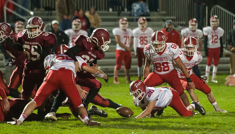 North Middlesex' Connor Claremont (20) tries to snare a fumble by Fitchburg's Damien Nadal (22) early in the 1st quarter at Crocker Field (SENTINEL&ENTERPRISE/ Jim Marabello)