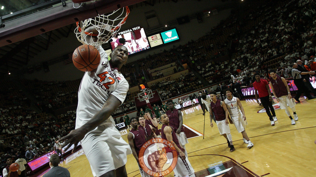 Ty Outlaw dunks the ball and hangs on the rim during pregame warmups as his teammates watch behind him. (Mark Umansky/TheKeyPlay.com)