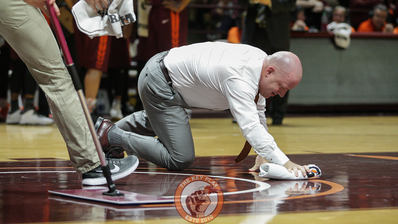 Buzz Williams helps wipe the floor up after Chris Clarke's injury. (Mark Umansky/TheKeyPlay.com)