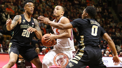 Justin Robinson gets between two Wake Forest defenders on a drive towards the basket. (Mark Umansky/TheKeyPlay.com)