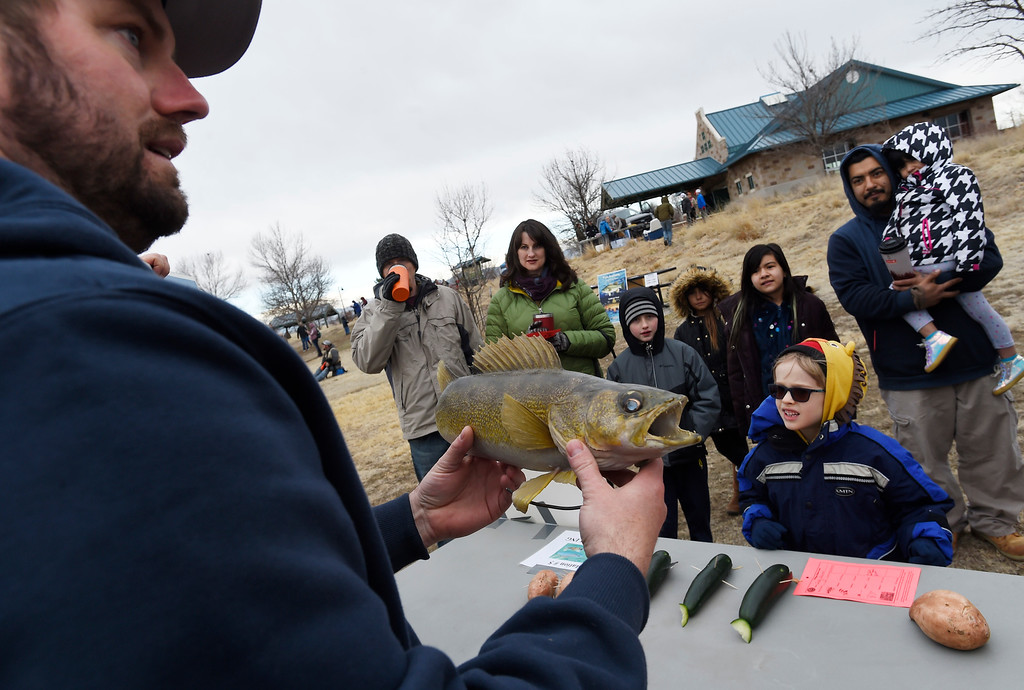 . Longmont, CO - March 23, 2019: Wilson Johnson, left,  explains how to handle a fish once you have caught it  during the 16th annual Chick Clark Kids� Fishing Program at Izaak Walton Pond in Longmont. For more photos, go to Timescall.com. (Photo by Cliff Grassmick/Staff Photographer)