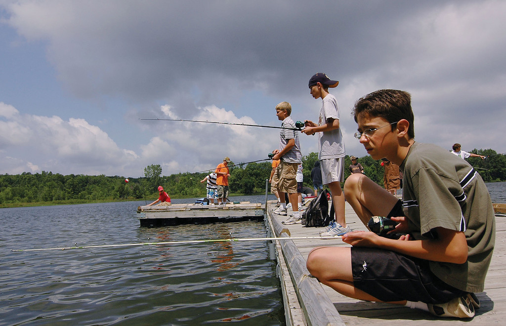 . 12-year-old Adam Macuga from Clarkston(right) and 12-year-old Ryne Jones of Clarkston fishes behind him at Independence Oaks County Park.    Special to the Oakland Press/ ERIN MASH