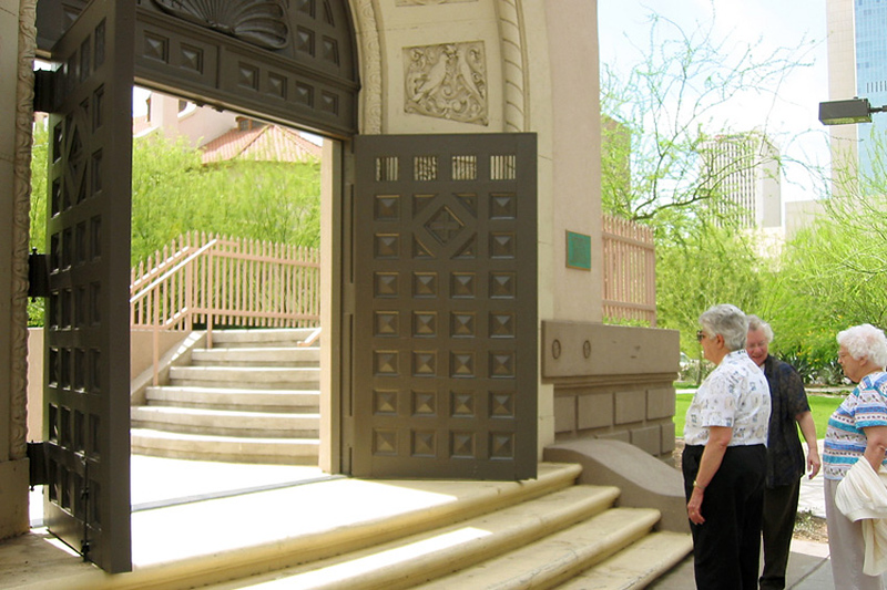 Sisters Janet Winandy, Anna Marie Sanders and Peg Williams look through the doors of the former St. Mary's Elementary School that double as the entrance to the Memory Garden where the school once stood. Numerous CPPS Sisters served at St. Mary's. Photo by Sister Judy Kroeger, C.PP.S.