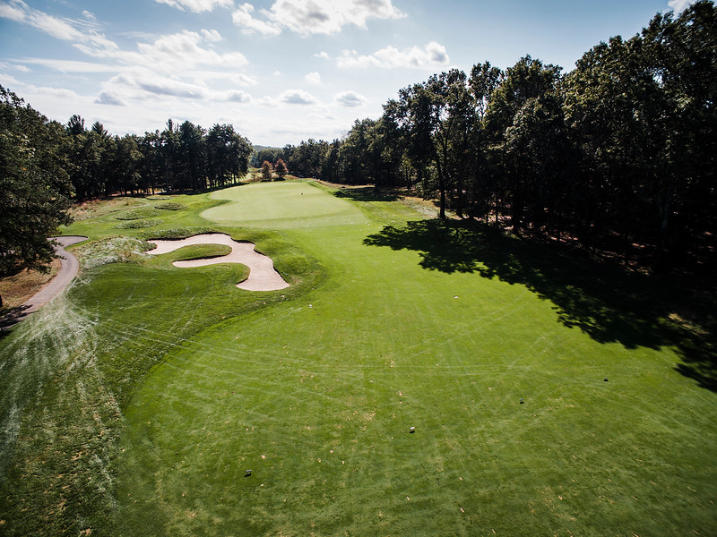 "The International<br /> Hole No. 5 Pines Course<br /> ""This par 5 measuring over 700 yards from the ""Tiger Tees"" is an<br /> impressively massive hole in more ways than its measurements. Most<br /> people play from the white tees, and certainly no slouch at nearly 600<br /> yards. A demanding drive is required, but your second shot is crucial<br /> in your endeavor to make par. At about 125 yards from the green, the<br /> hole sharply doglegs left so the second shot ideally requires a little<br /> bit of a draw. If executed well, you will have inside 150 yards to<br /> this half-acre of green. Front to back of this green is almost a<br /> five-club difference. A back or even middle pin placement, could<br /> create well over an 80-foot putt at times. Quite honestly, a<br /> spectacular hole that will give you a sense of accomplishment upon<br /> successful completion."" -- Brendan Reilly, Director of Golf at The<br /> International<br /> SENTINEL & ENTERPRISE / Ashley Green"