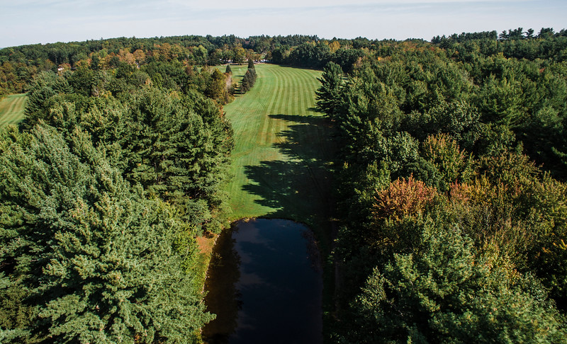 """Settlers Crossing<br /> Hole 9<br /> """"The 9th hole at Settlers Crossing plays as a par 5 from the back tees at 490 yards. The first 125 yards features a pond in front of the tee box and a narrow opening. A mis-hit off the tee will leave you either in the water, the woods or heavy rough. The fairway looks quite expansive beyond that and the look of it encourages players to really let it fly but there are trees and rough on both sides that can cause trouble. The landing area of most drives will slope to the left and many balls will end up in the rough making it very difficult to reach in 2 for even the longest players. The green is fairly large with<br /> enough slope to make an up and down a challenge. From the side tees, the hole plays as an even more challenging 430 yd. par 4. Players may try to cut the corner to the left, but will usually end up in heavy<br /> rough if they do so. Even a good drive will leave a 200-yard plus approach shot to the green."""" -- Bill Gustas, Owner/Manager Settlers Crossing<br /> SENTINEL & ENTERPRISE / Ashley Green"""