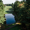 "Settlers Crossing<br /> Hole 9<br /> ""The 9th hole at Settlers Crossing plays as a par 5 from the back tees at 490 yards. The first 125 yards features a pond in front of the tee box and a narrow opening. A mis-hit off the tee will leave you either in the water, the woods or heavy rough. The fairway looks quite expansive beyond that and the look of it encourages players to really let it fly but there are trees and rough on both sides that can cause trouble. The landing area of most drives will slope to the left and many balls will end up in the rough making it very difficult to reach in 2 for even the longest players. The green is fairly large with<br /> enough slope to make an up and down a challenge. From the side tees, the hole plays as an even more challenging 430 yd. par 4. Players may try to cut the corner to the left, but will usually end up in heavy<br /> rough if they do so. Even a good drive will leave a 200-yard plus approach shot to the green."" -- Bill Gustas, Owner/Manager Settlers Crossing<br /> SENTINEL & ENTERPRISE / Ashley Green"