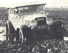 Touring car (?) stuck in mud