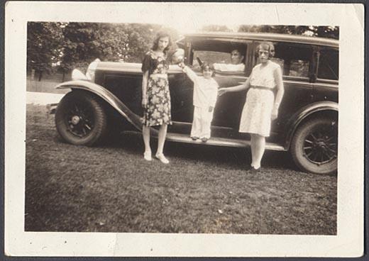 3 ladies standing beside a 29 Sedan (note missing hubcap on rear wheel)