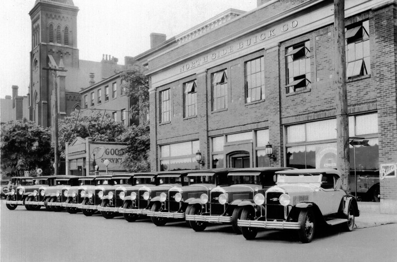 An original 1928 photo of a Buick dealership in Pittsburg, PA. and several things are interesting:  1) All 10 Buicks have the radiator badge put on 29's before then factory discontinued attaching them on Sept. 19, 1928.  2) None of the cars show any exterior options (rad caps, sidemounts, rims, spotlights, etc.)  Even the showroom car appears to have no sidemounts.  3) All cars appear to have the factory standard issue artillery wood rims (today, often confused with the optional demountable at the hub, wood wheels). 4) There appears to be a variety of car colors (B&W shades). 5) There is a Silver Anniversary poster in the showroom window. 6) All the Buicks, with the exception of one, have a note on the passenger front widow (price?). 7) The original Buick sign, shown on the building, sold for $9,500 in early 2019 ! (Thanks to Norm McKendry)