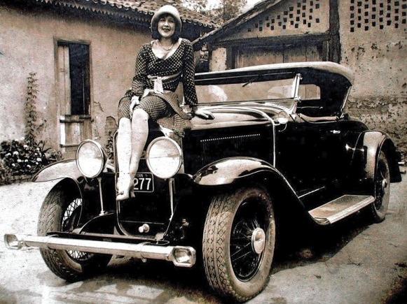 """29-44 - The charming photo taken in Brazil shows us """"Miss JF (after Juiz de Fora"""", a city also known as J.F. in the southeastern Brazilian state of Minas Gerais, located close to the state border with Rio de Janeiro). She is posing on top of the rad of a sporty 1929 Buick roadster.  She is wearing a polka-dotted dress, high heels and an attractive hat, all in the fashion of the time.  The Buick is equipped with quite an expensive accessory bumper with driving lights in either end.  The photo is courtesy of Marcelo Lemos via Guilherme de Costa Gomes' site ."""