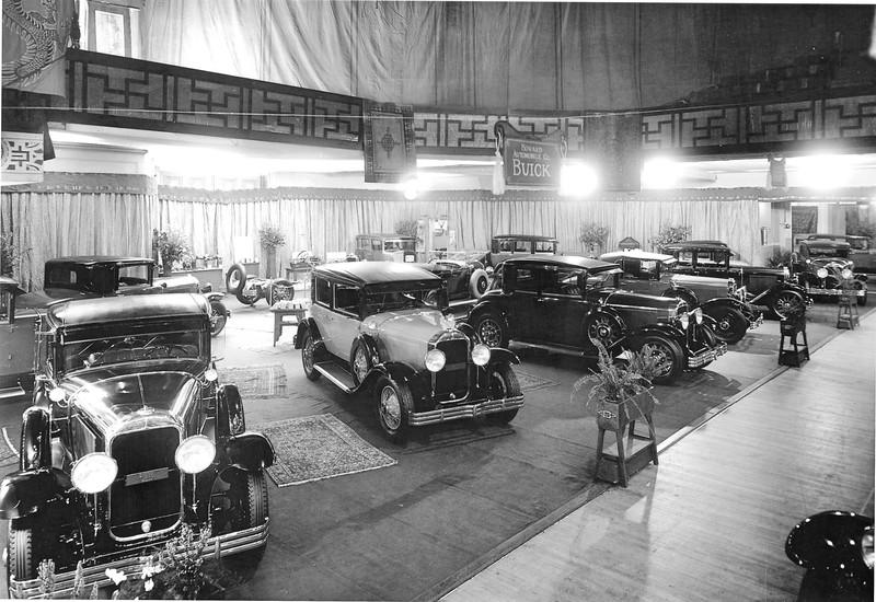 Photo sent by Norm McKendry (54CC).  Howard Buick's display at the San Francisco Auto Show (Jan.26 - Feb. 2,1929). Noteworthy are: 1) Many cars have the windwing option (assume W/W's were put on by Howard's SF dealership).  2) Note the chassis and Fisher body displays in the background.  3) The model 44 (at the center rear) has an unusual light (tan?) sidemount and boot cover which I was black on all models.  4) All cars have the star hubcaps and flip-top rad cap Both late.  5) Literature on a table near the centre.  6) Since the radiator emblems were discontinued on Sept. 16, '28, the ends were removed and the center portion attached to the fern stands in the foreground.  7) There are 14 out of 19 Buicks models in the photo and presumably more to the left.  8) The cars are outfitted with the new tread Goodrich Silvertown tires.