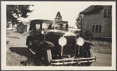 29 Buick Sedan near 2 houses (note 2 bar bumper)