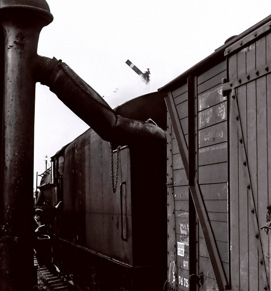 Taking water, Carnforth, August 1967.    A Stanier loco fills its tender from the LNWR water column at the south end of the up WCML platform.  NB the 'Shunt Care' label on the van.