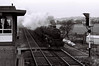 45455, Hest Bank, 25 March 1967.    The signalman is on what used to be called the 'blower' as the Black 5 heads south.  It lasted until August.  The signal box opened in 1958, when it replaced a LNWR box south of the station.  The boarded crossing was for use by the signalman when issuing or receiving the token for the single track line to Bare Lane.  It had been removed by September 1967, when token working had finished.  NB the signal box chimney for its coal-fired stove.  The chimney was removed when electric heating was installed, date unknown.