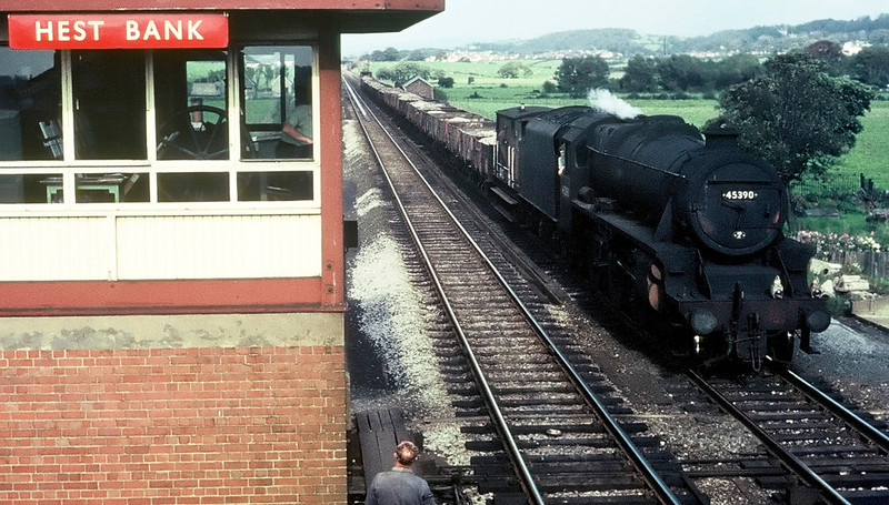 45390, Hest Bank, August 1967.  The Black 5 heads south while the signalman talks to a chap at ground level.  Visible in the box are the lever frame and the wheel for operating the level crossing gates.  NB that the boarded crossing seen in my 25 March photo has been removed following the end of token working on the Bare Lane spur.  Hest Bank troughs can be seen in the distance.  45390 lasted to the end of steam in August 1968.