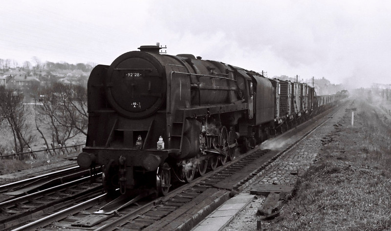 92128, Hest Bank, 25 March 1967.    The northbound freight passes the end of Hest Bank troughs after picking up water.  The 9F sports a painted 10A (Carnforth) shed code.  It lasted until December.