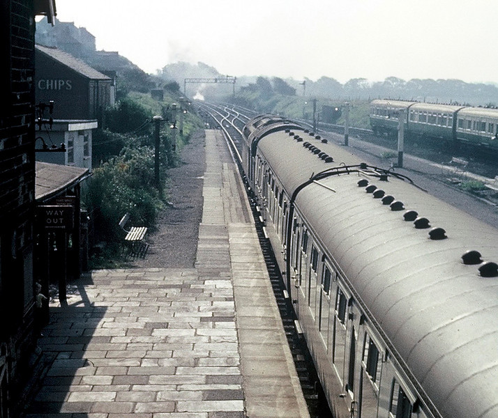 Hest Bank August 1967.  An unidentified English Electric Type 4 (Class 40) whistles south. The station was still open, though hardly any trains called.  Note the smoke in the distance from a train waiting to come off the branch from Bare Lane.