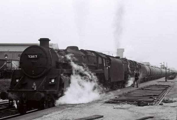 73157 & 92077, Holbeck Low Level, Sat 29 April 1967.  The Heysham - Hunslet East oil train pauses at the closed station to detach the pilor loco, which will have run to Holbeck shed. According to its painted 9H shed code, 73157 was allocated to Patricroft at the time.  It was withdrawn in May 1968.