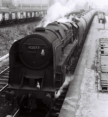 92077, Holbeck Low Level, Sat 29 April 1967.  The 10A (Carnforth) loco prepres to take the tanks to Neville Hill.  From there they will have been tripped to Hunslet East by local diesel shunters. The 9F was withdrawn in June 1968.