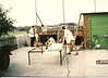 Dave Dawe (far left) Richard Burkin with no top. Possibly Trevor Greenland in the trailer, Paul Mapstone (ASL) kneeling and Adrian Slaughter with the saw. They are building John's Dustcart Trailer.
