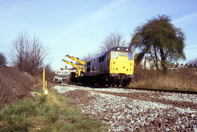 31297 manouevres a mobile crane into position during track renewals half a mile to the south of Bingley station. The location is the former foot crossing at Southfield Lane (18/04/1982)
