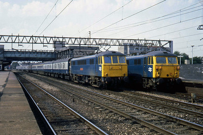 86209 'City of Coventry' leads a Euston-bound express through the middle road at Stafford as 87004 waits in Platform 1 (22/07/1983)