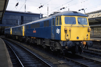 87005 'City of London' leads a line of AC Electrics at Carlisle (15/04/1984)