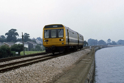 142020 passes Cockwood Harbour with the 1020 Exeter - Paignton (11/08/1986)