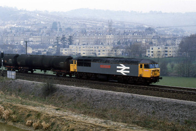 56053 'Sir Morgannwg Ganol/County of Mid Glamorgan' heads east through the outskirts of Bath with a train of oil tanks (22/02/1988)