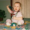 Jinny playing with a pile of Mardi Gras beads - Lake Charles, LA  Jan 1989