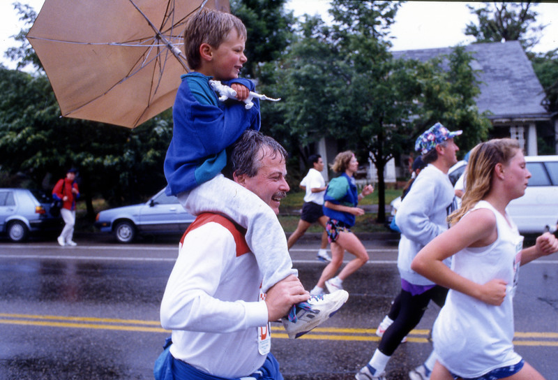 A young man get a ride as he uses an umbrella during the 1992 Bolder Boulder.