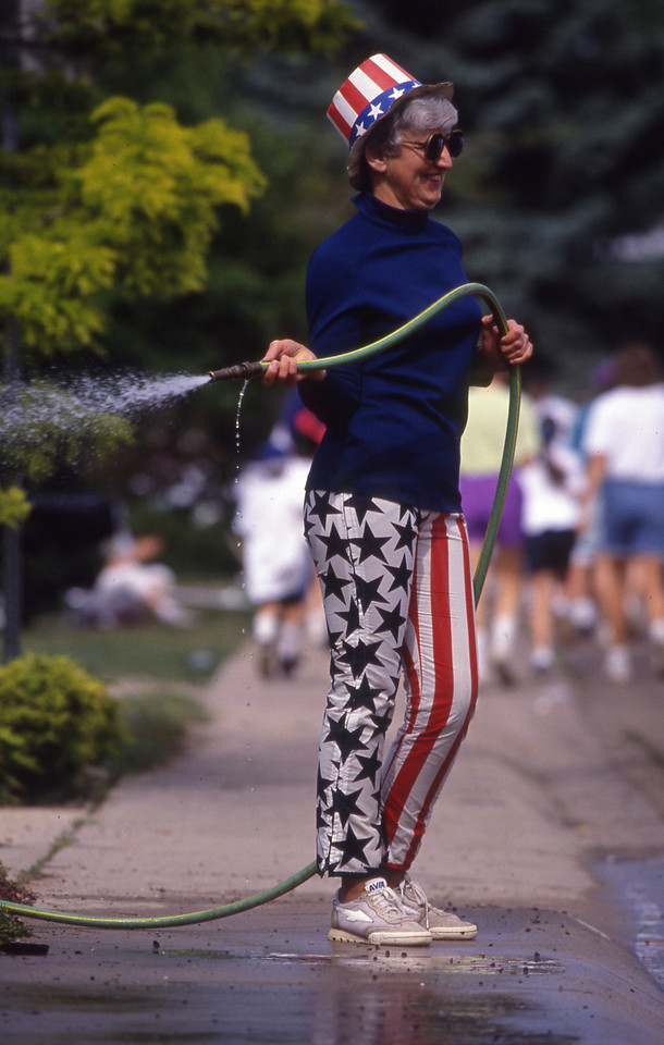A women wearing attire for the Memorial Day holiday readies to spray down the runners in the 1993 Bolder Boulder.