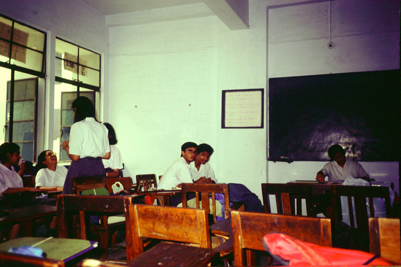 Sanghamitra (with glasses, laughing), Kartikeya (with glasses) sitting next to Archis (both looking at camera), Madhura (at teachers' desk)