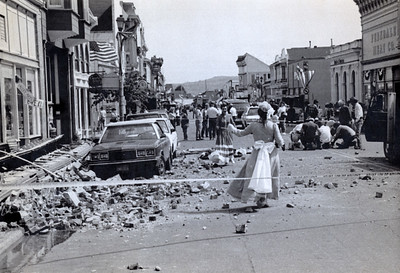 "A woman in costume for Ferndale's annual ""Best of the West Fest"" looks on as rescue workers tend to a man hurt by falling stonework on Main Street. The victim was one of scores injured by the quakes, the Times-Standard reported on April 26, 1992. (Times-Standard file photo)"