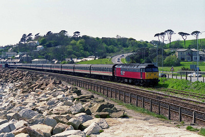 Having run round at Long Rock, 47761 is seen propelling the empty train back into Penzance station. The rocks in the foreground are part of the enhanced sea defences protecting the line (11/05/1996)