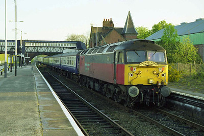 Hooton, Merseyside, is the unusual setting for 47763 as it waits to depart with 1Z69 0720 charter to Minehead (18/04/1998)