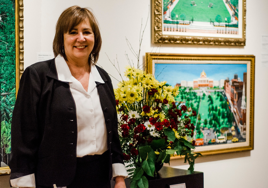 . Joan David stands in front of her floral interpretation on display at Fitchburg Art Museum\'s 19th Annual Art in Bloom on Friday, March 31, 2017. SENTINEL & ENTERPRISE / Ashley Green