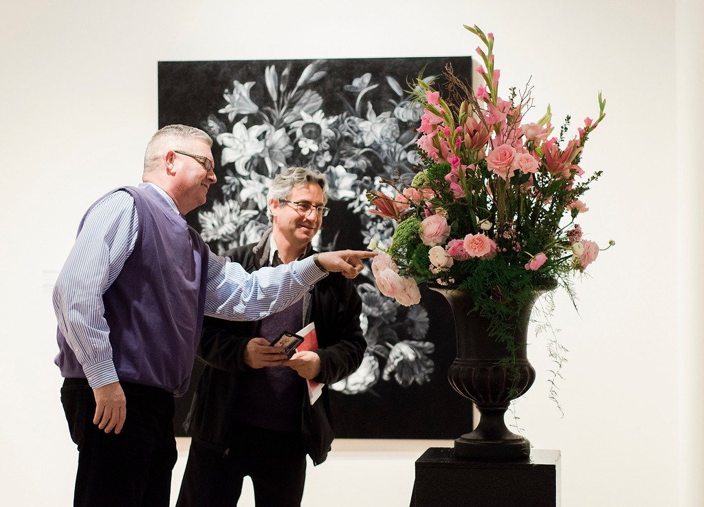 . State Representative Stephan Hay and Darron Massey take a closer look a floral interpretation of \'Garland with Bird\' by Joan Pease and Debbie St. Vrain at  Fitchburg Art Museum\'s 19th Annual Art in Bloom on Friday, March 31, 2017. SENTINEL & ENTERPRISE / Ashley Green