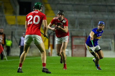 Cork's Robert Downey passes the ball to team mate Mark Coleman watched closely by Tipperary's John McGrath