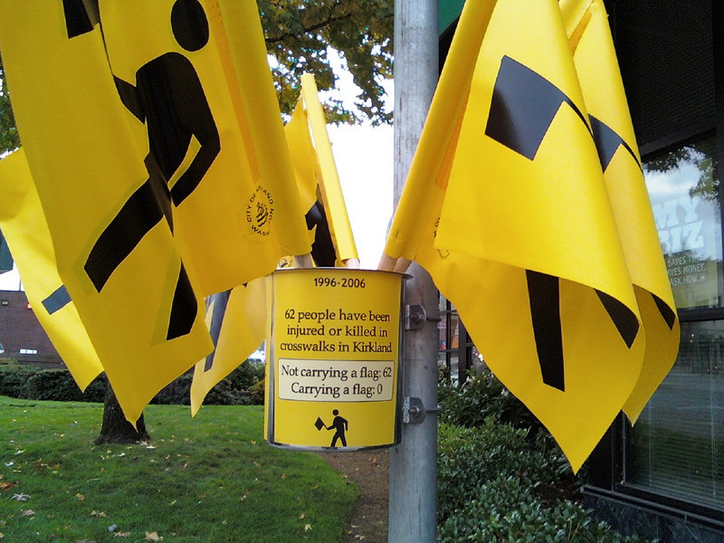 """In 1995, Kirkland, Wash., became the first U.S. city to implement a pedestrian flag program when it started PedFlag to reduce the number of pedestrian injuries and deaths. The program provides flags at more than 50 crosswalks throughout the city for pedestrians to carry as they cross the street, thereby increasing their visibility to cars. The City of Kirkland maintains the flags at downtown locations, and the other sites are maintained by citizen volunteers. <br /> <br /> In 2006, the PedFlag program received TE funds, under Category 2,  to develop, implement, and increase the use of pedestrian flags at crosswalks. The study resulted in a flag redesign, and strategies for program promotion and partnerships with local businesses. Federal Award: $60,000; Local Match: $0; Total: $60,000<br /> <br /> For more information about the PedFlag program, visit: <a href=""""http://www.ci.kirkland.wa.us/depart/Public_Works/Transportation___Streets/Pedestrian_Flags_-_FAQs.htm"""">http://www.ci.kirkland.wa.us/depart/Public_Works/Transportation___Streets/Pedestrian_Flags_-_FAQs.htm</a><br /> <br /> Check out this news story about the PedFlag program on YouTube: <a href=""""http://www.youtube.com/watch?v=FAy4Bxo6FTg"""">http://www.youtube.com/watch?v=FAy4Bxo6FTg</a><br /> <br /> Photo credit: City of Kirkland"""