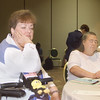 Thursday, July 11, 2002. Philadelphia, PA. Photos by Mike Levin.- Perspectives for the Differently-Abled- Marriott hotel,  Salon K & L. - (left-right )Pat Foley (in wheelchair) prayerfully reflects and Visually impaired participant Rita Pennington from Denver. CO takes notes while  listening to speaker Laura Rorem from Juneau, Alaska speak about Mental Illness and brain disorders.