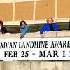 red cross landmine week in saturday dave milne feb 22 02 Red Cross volunteers, with the help of acting mayor,  Councillor Shirley Gratton, hang a banner on the library declaring february 25-March 1 Canadian Landmine Awareness Week.  Helping hang the banner are Katherine Walraven, left, Sanna Vierimaa, Danielle Evanoff, Councillor Shirley Gratton, Anita Muchalla and Sarah White, International Service Coordinator for the Red Cross.