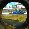 PGARA time trials in monday dave milne aug 23 03 Flagman Bill Van Helvoirt gives 53 the checkered flag after time trial laps Saturday. Photo taken through one of the large tires lining the inside of the track.
