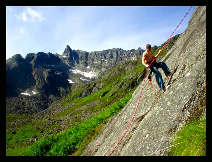 A hot August sun warms the rock as Ben Bates rappels down <i>Local Motion 5.5</i> in Archangel Valley.